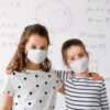 Two children standing in front of smart antimicrobial whiteboard paint