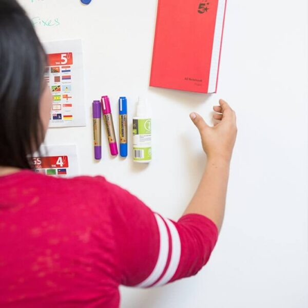 Woman hanging up notebook on smart magnetic plastered wall