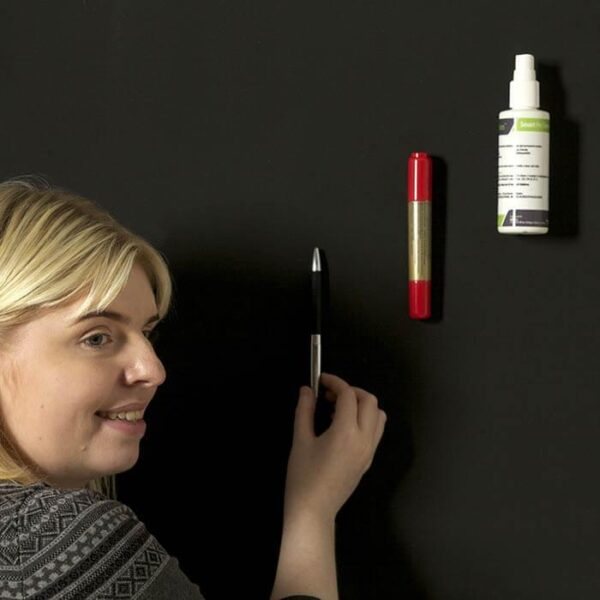 Woman sticking up items on super magnetic painted wall
